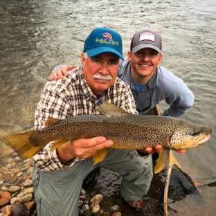 Fly fishing guide and client with a large trout in Missoula, MT