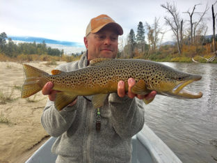 Man in hat holding large brown trout